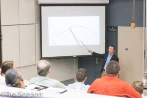 """Dr. Adam Johnston shows a chart on the trajectory of a dancer's center of mass during his """"Physics of the Mudane"""" seminar.(The Signpost/ Christina Huerta)"""