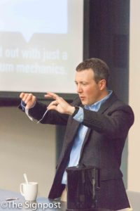 """Dr. Adam Johnston uses tape to demonstrate electron attraction during his """"Physics of the Mudane"""" seminar.(The Signpost/ Christina Huerta)"""