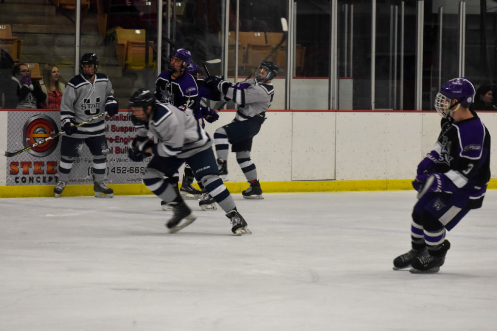Thomas Simpson looking on as team member Joel Johnson fights to get to the puck.  (Nikki Dorber / The Signpost)