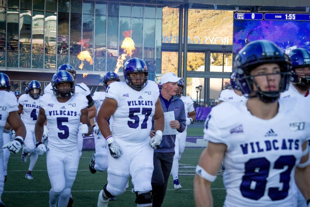 The Weber State Wildcat football team runs onto the field before the game begins while pyrotechnics erupt in the background. (Kalie Pead/ The Signpost)
