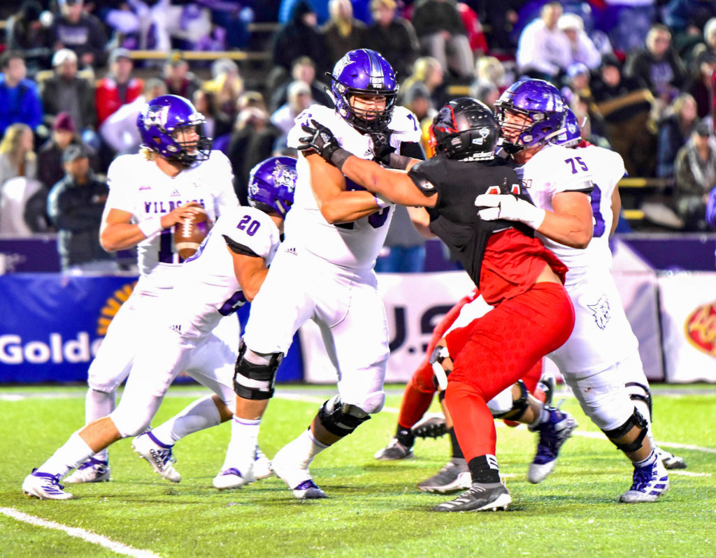 Ty Whitworth, number 75, Josh Davis, number 20 move work together to move the ball. (Nikki Dorber / The Signpost)
