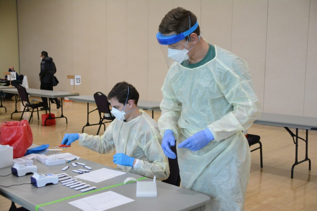 Health care professionals sort and label finished testing materials. (Brooklynn Kilgore/The Signpost)