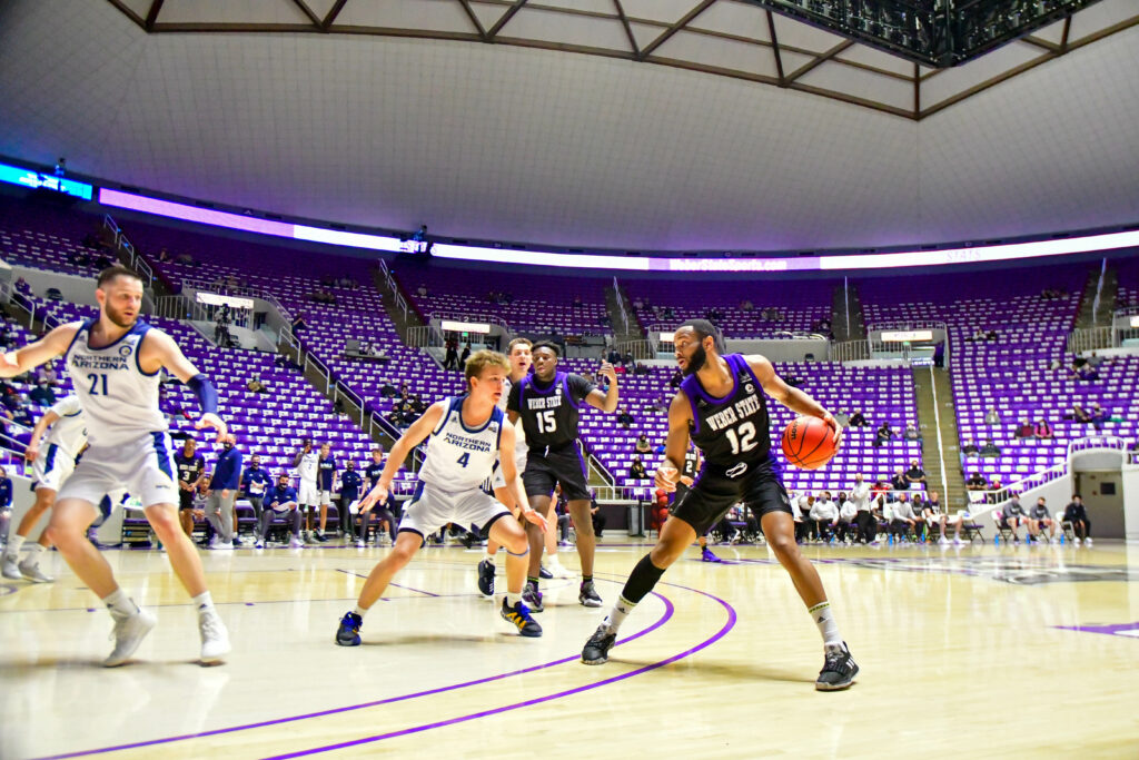 Weber State's Isiah Brown, number 12, preparing to set for a three pointer in Saturday's game against Northern Arizona.  (Nikki Dorber / The Signpost)