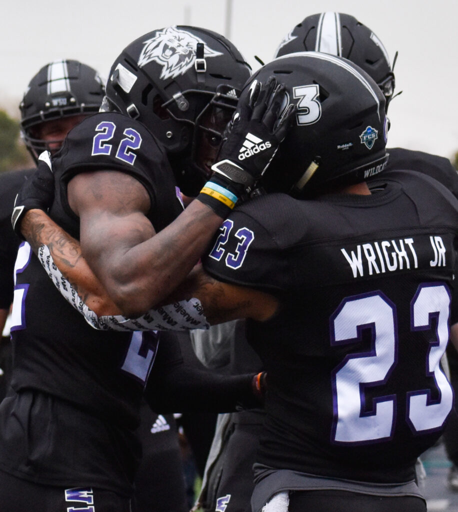 Helmet bumps between two Weber State University football players on Saturday at Stewart Stadium. (Paige McKinnon/The Signpost)