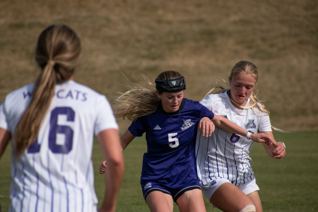 Two players fight for the ball, shoulder to shoulder ,on the Weber State soccer field on March 19. (Paige McKinnon/The Signpost)