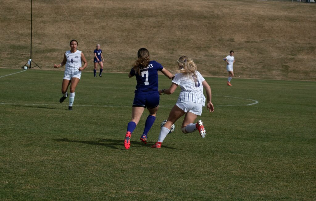 Two wildcat players, on different teams for their scrimmage, go head to head for the ball. (Paige McKinnon/The Signpost)