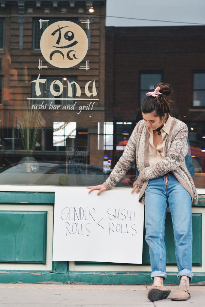 "Mak holds a sign reading ""gender roles < sushi rolls,"" Sunday, Mar. 14, 2021, in Ogden, Utah. (Brooklynn Kilgore/The Signpost)"