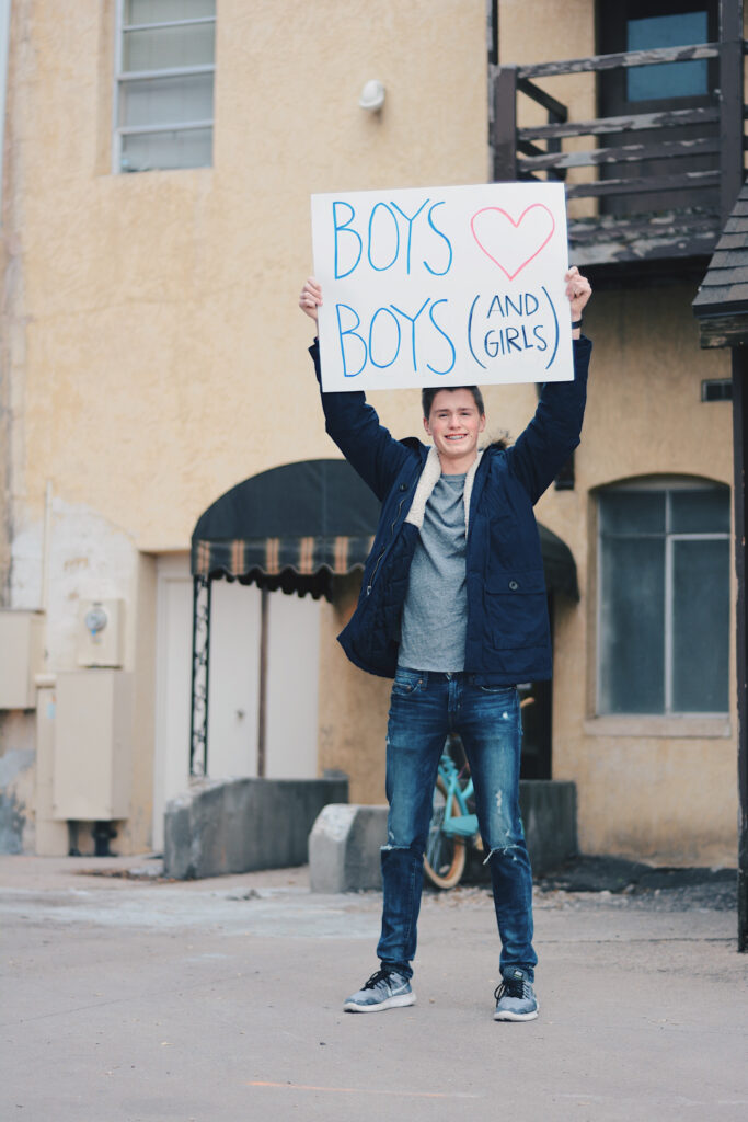 "Braeden Budge holds up a poster that reads ""BOYS ♡ BOYS (AND GIRLS),"" Sunday, Mar. 14, 2021, in Logan, Utah. (Brooklynn Kilgore/ The Signpost)"