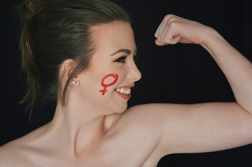 Brooklynn Kilgore flexes her bicep, bearing a female symbol on her cheek, Sunday, Mar. 14, 2021, in Ogden, Utah. (Brooklynn Kilgore/The Signpost)