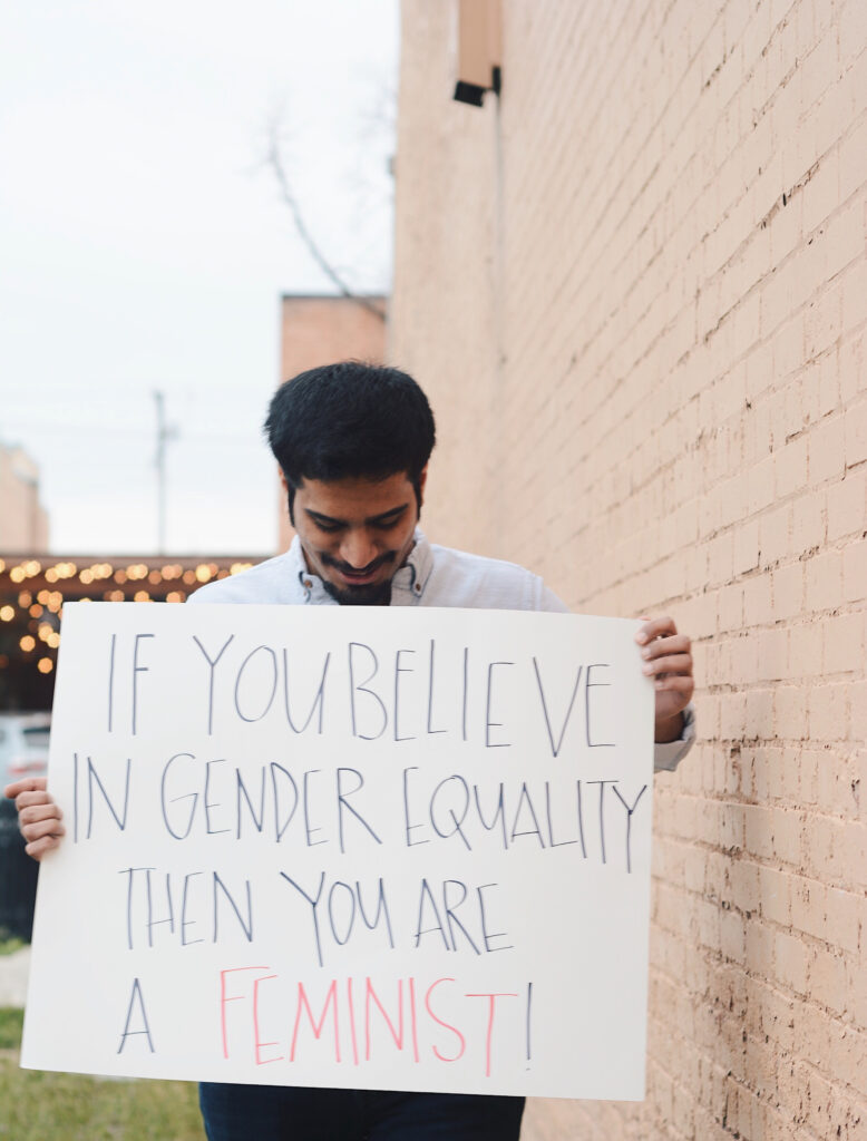 "Azzam holds a sign reading ""If you believe in gender equality then you are a feminist!,"" Sunday, Mar. 14, 2021, in Ogden, Utah."