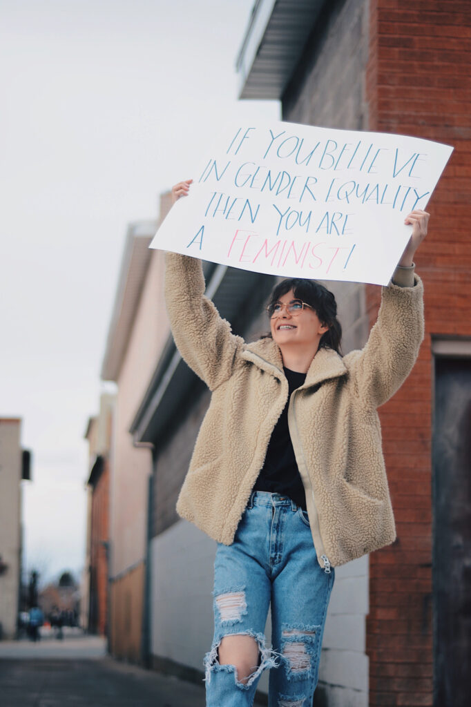 "Emily Daines grasps a sign reading ""If you believe in gender equality then you are a feminist!,"" Sunday, Mar. 14, 2021, in Logan, Utah. (Brooklynn Kilgore/ The Signpost)"