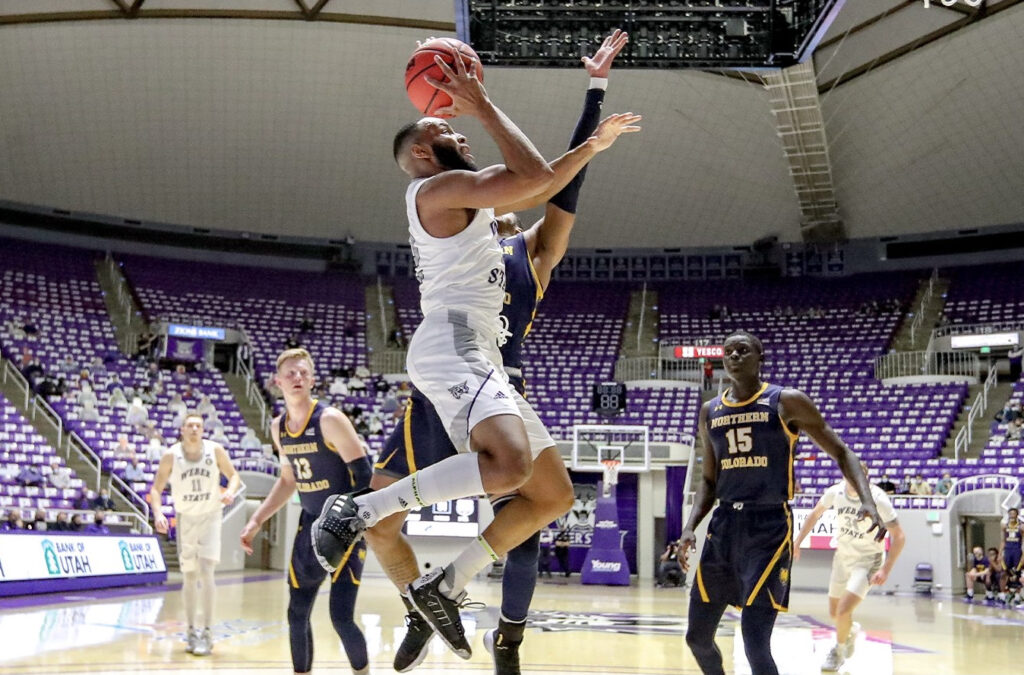 Wildcat's guard Isiah Brown taking the basketball to the hoop through traffic against NCU.