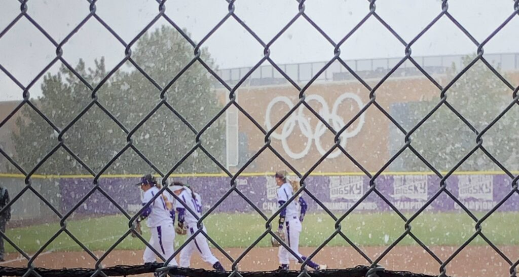 Wildcat softball players running to the dugout as snow falls forcing the game to be canceled in Ogden on March 23.