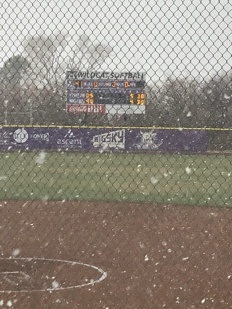 Snow falling at Wildcat softball field after the game was canceled due to the weather.