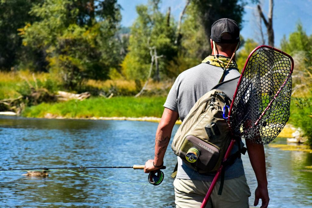 A fisherman is walking along the river, finding a spot to fish. Nikki Dorber/The Signpost