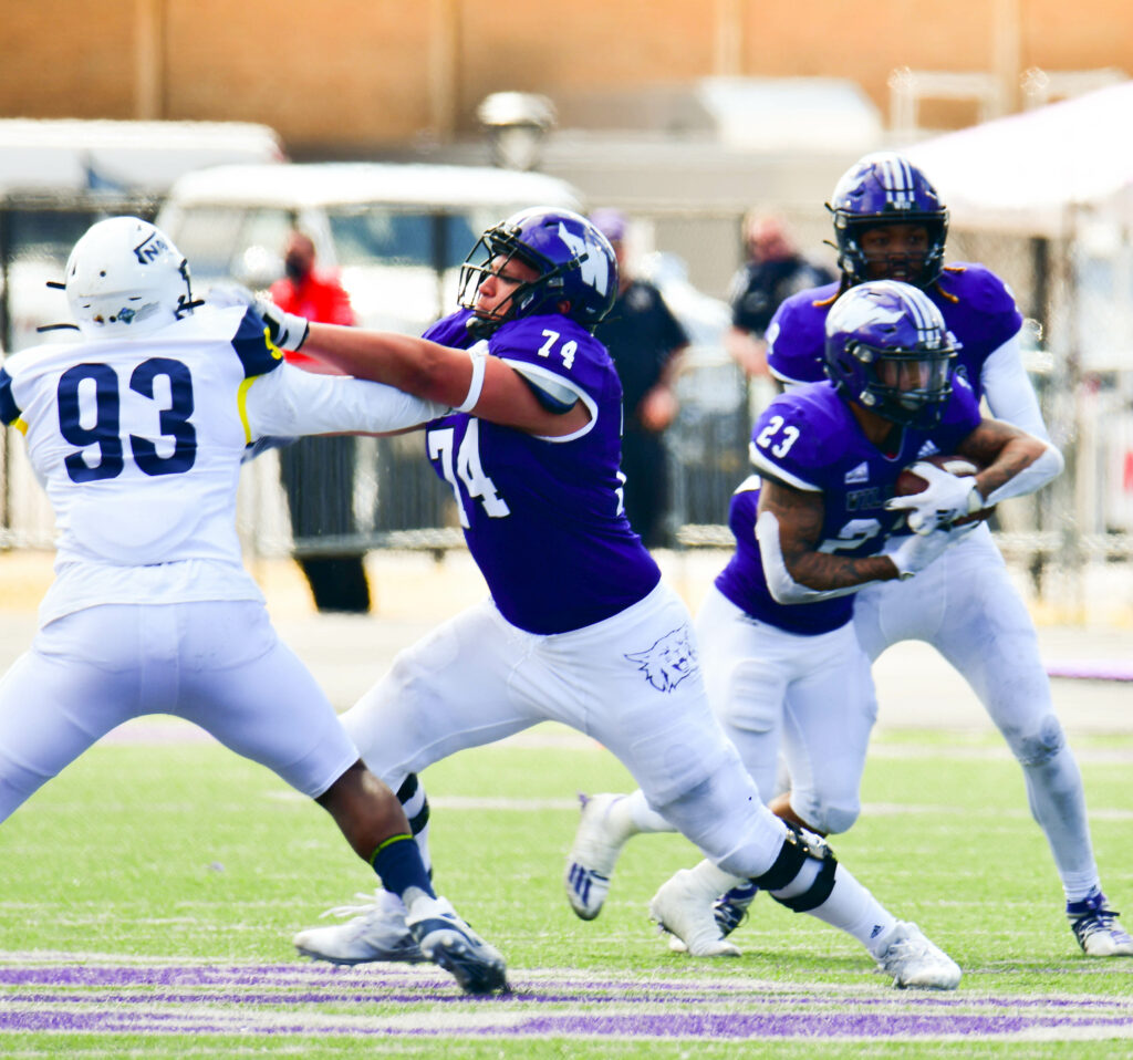 Weber State University's offensive lineman George Barrera protects running back Daniel Wright Jr. as he gains yards during one of many drives during the game against Northern Arizona University on Saturday, March 27. Nikki Dorber/The Signpost