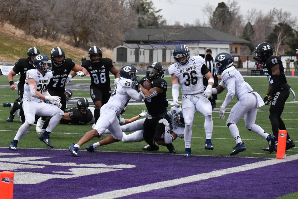 Weber State football player Dontay Wright Jr. makes a touchdown despite the pushback from the Aggies. (Paige McKinnon/The Signpost)