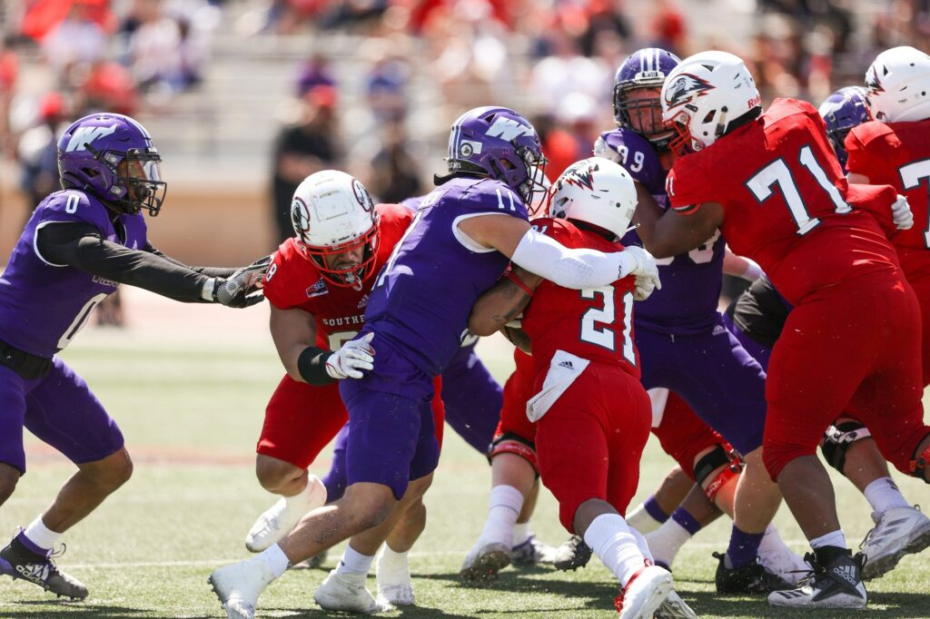 Wildcat linebacker #11 Conner Mortensen wraps up SUU running back #21 Jay Green Jr. as Wildcat safety #0 Desmond Williams looks for a tackle at Eccles Coliseum in Cedar City on April 3.