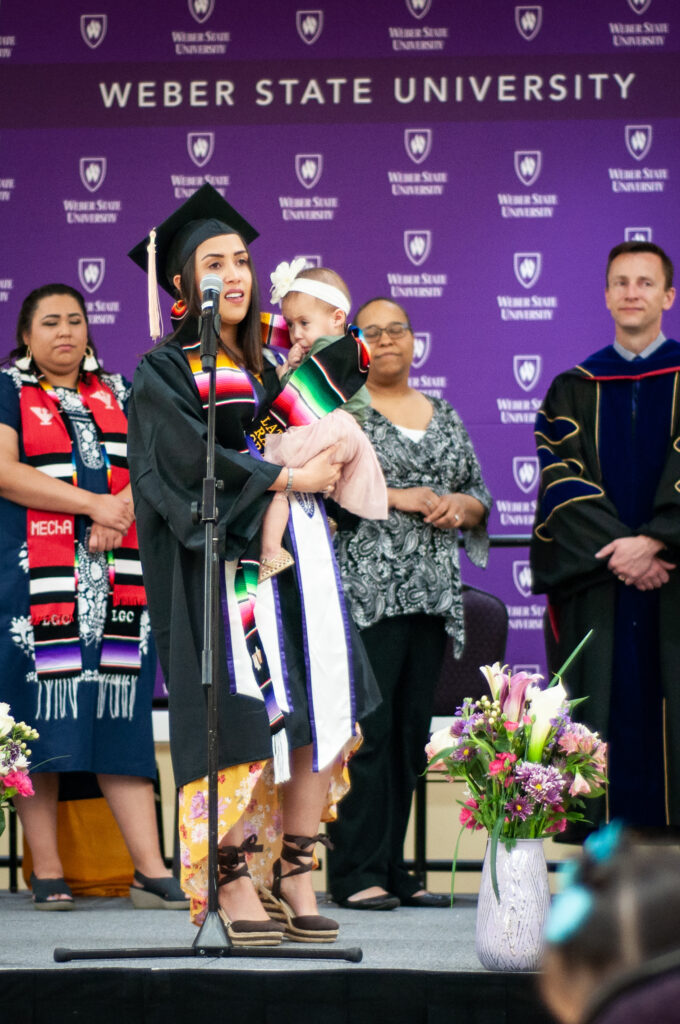 A Latinx graduate walking across the stage with her child was a memorable moment during a past ceremony.