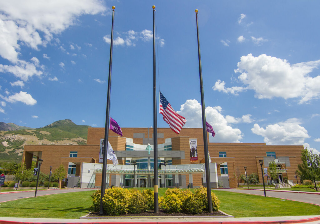 Weber State and United States of America flags wave in the wind right outside the Browning Center on WSU main campus in Ogden, UT.