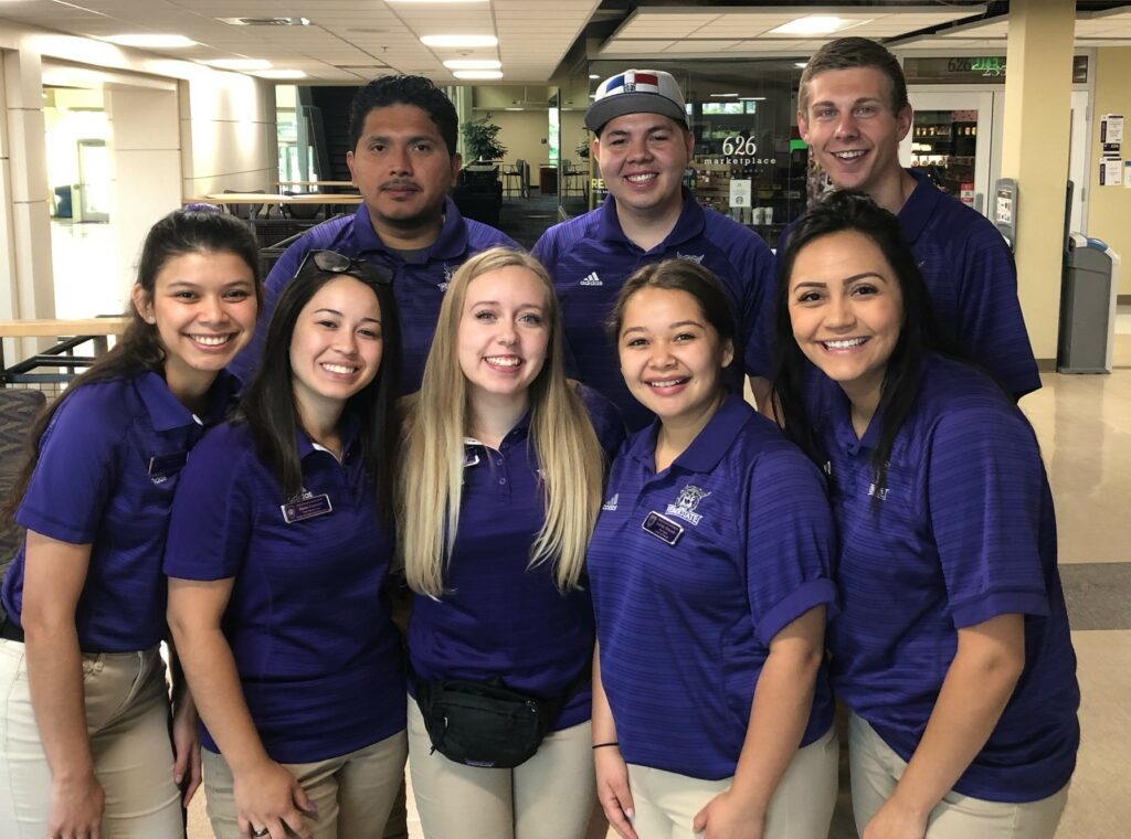 A past group of peer mentors welcomes students during orientation.