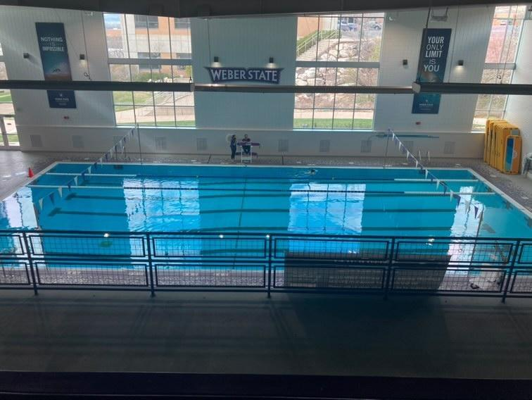 Lifeguards sit on the edge of Swenson Pool inside the Stromberg Complex at Weber State University.