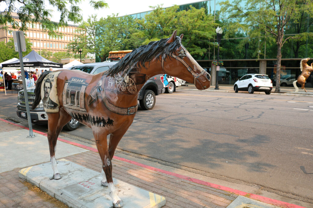"""Junior Layton High School student Michel Collins, a fifteen-year cancer survivor, is the artist behind """"Wanted."""" Wanted is one of the many horses located along 25th street in Downtown Ogden. (Bella Torres / The Signpost)"""