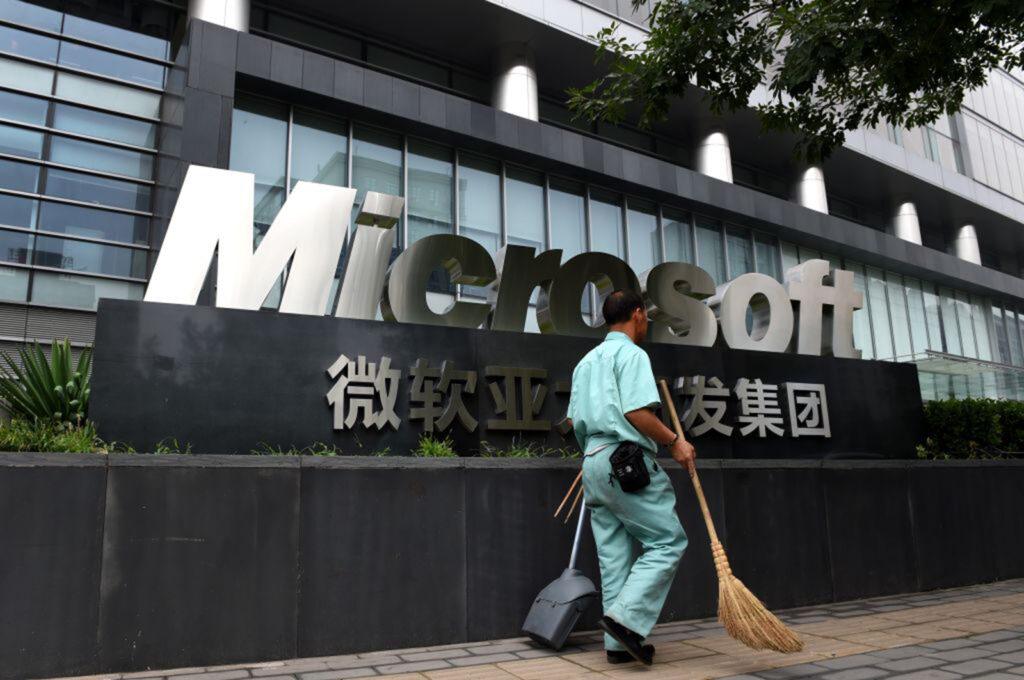 A cleaner walks past a Microsoft sign outside a Microsoft office building in Beijing on July 31, 2014.
