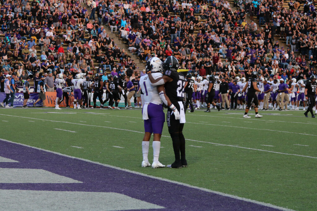Though tensions were high between the Dukes and the Wildcats, JMU's Scott Bracey (#1) and WSU's Rasheed Shaheed (#22) find time to exchange a friendly embrace, embodying true sportsmanship. (Bella Torres / The Signpost)
