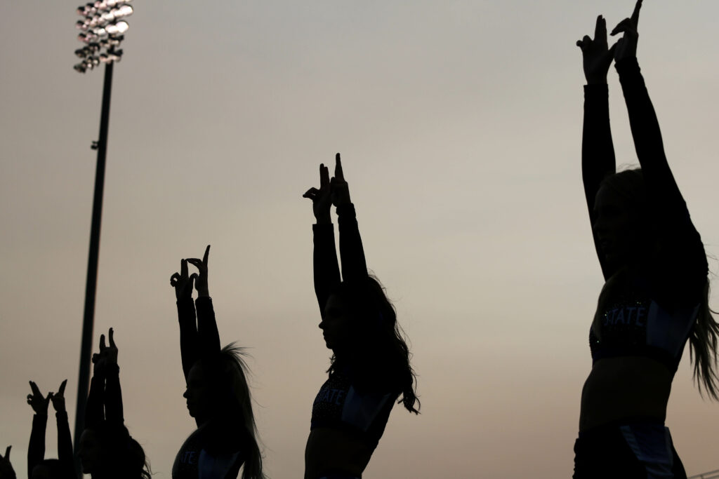 """The Wildcat cheer team lines up for kickoff with their """"W&squot;s"""" up high. (Bella Torres / The Signpost)"""