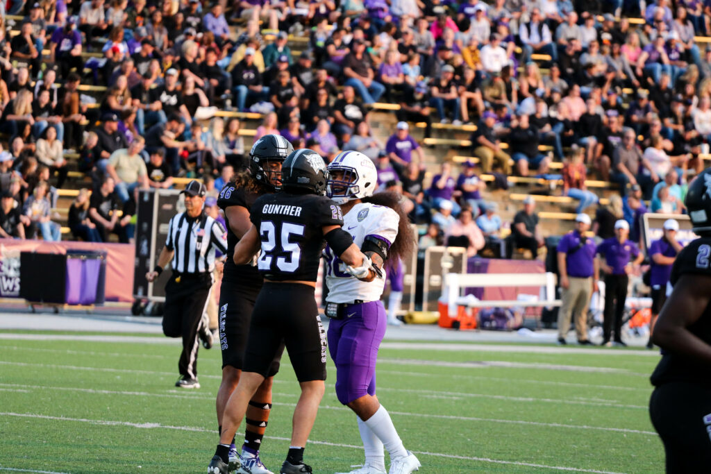 An intense exchange between Weber's Braxton Gunther, 25, and James Madison's Seth Naotala, 46, requires intervention as tensions rise. (Bella Torres / The Signpost)