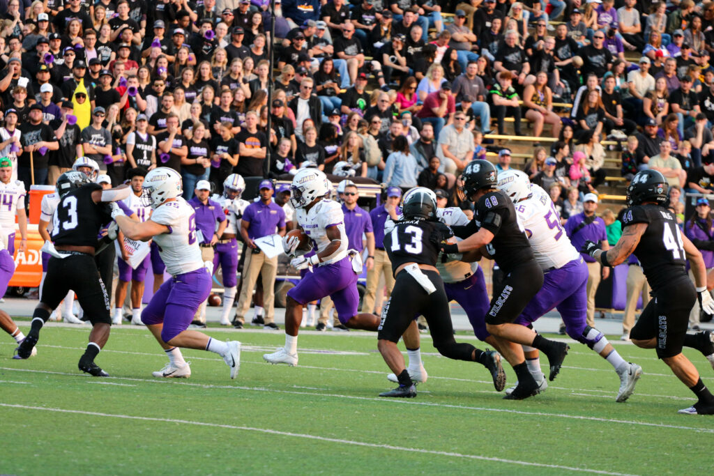 James Madison's offense rushes the ball against Weber State's defense. (Bella Torres / The Signpost)