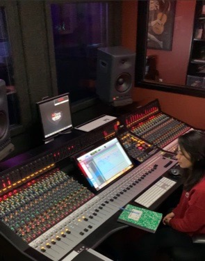 Callie Oyama at the Neve sound console. While it used to be housed in a small lab for the Sound Production/Recording students, it is now in storage awaiting the completion of the new recording studio.